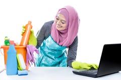 使用膝上型计算机的多任务主妇,当拾起一个瓶分类时 库存图片