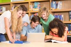 使用膝上型计算机的大学生在图书馆 图库摄影