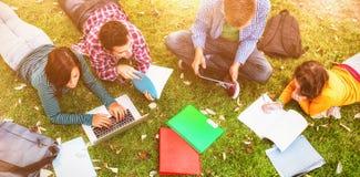 使用膝上型计算机的大学生,当做家庭作业时 免版税库存图片