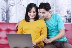 使用膝上型计算机的夫妇在冬天季节 免版税库存照片