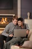 使用膝上型计算机的夫妇在冬天 库存图片