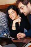 使用膝上型计算机的夫妇在咖啡馆 免版税图库摄影