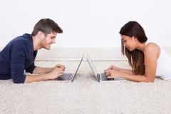 使用膝上型计算机的夫妇在地毯 库存照片