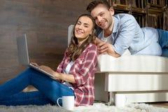 使用膝上型计算机的夫妇在家和微笑对照相机 免版税图库摄影