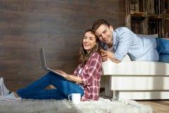 使用膝上型计算机的夫妇在家和微笑对照相机 免版税库存照片