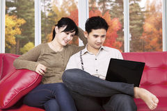 使用膝上型计算机的夫妇在家在秋天 图库摄影