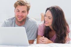 使用膝上型计算机的夫妇在床上 库存照片