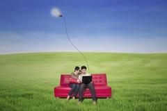 使用膝上型计算机的夫妇在有室外的灯的红色沙发 免版税库存照片