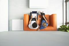 使用膝上型计算机的夫妇在橙色沙发在办公室 库存图片