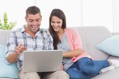 使用膝上型计算机的夫妇在沙发的电视电话会议的 库存图片
