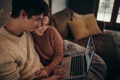 使用膝上型计算机的夫妇在hygge房子里 图库摄影