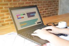使用膝上型计算机的女商人为分析财政图表趋向预测计划在咖啡从窗口的咖啡馆阳光 库存图片