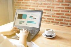使用膝上型计算机的女商人为分析财政图表趋向预测计划在咖啡从窗口的咖啡馆阳光 库存照片