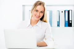 使用膝上型计算机的女商人在办公室 免版税库存照片