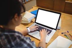 使用膝上型计算机的女学生在图书馆 图库摄影