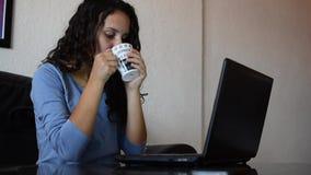 使用膝上型计算机的女孩和喝咖啡 影视素材