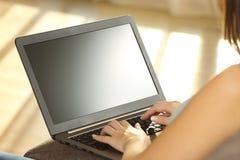使用膝上型计算机的女孩和显示一台空白的显示器 库存图片