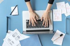 使用膝上型计算机的女孩在办公室 免版税库存照片