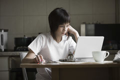 使用膝上型计算机的女孩在厨房 免版税图库摄影