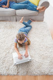 使用膝上型计算机的女孩,当在家时说谎在地毯 免版税库存照片