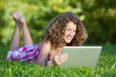 使用膝上型计算机的女孩,当说谎在草时 免版税库存图片