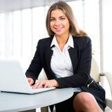 使用膝上型计算机的女实业家在办公室 免版税库存图片