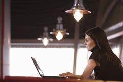 使用膝上型计算机的女实业家在咖啡馆 免版税库存照片