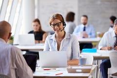 使用膝上型计算机的女实业家在顾客服务部 免版税库存图片