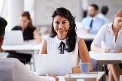 使用膝上型计算机的女实业家在顾客服务部 库存照片
