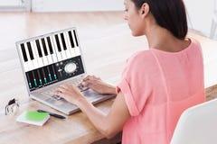 使用膝上型计算机的女实业家的综合图象在书桌在创造性的办公室 免版税库存图片