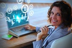 使用膝上型计算机的女实业家的综合图象在书桌在创造性的办公室 免版税库存照片