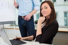 使用膝上型计算机的女实业家,当给介绍时的同事 免版税库存照片