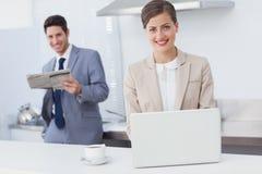 使用膝上型计算机的女实业家,当食用早餐时 免版税库存照片
