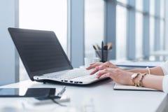 使用膝上型计算机的女工在办公室,与新的项目一起使用 妇女在家blogging作为自由职业者 免版税库存图片