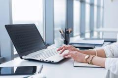 使用膝上型计算机的女工在办公室,与新的项目一起使用 妇女在家blogging作为自由职业者 图库摄影