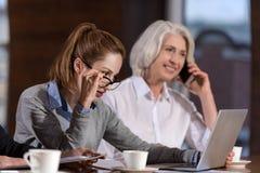 使用膝上型计算机的女性同事和谈话在工作 库存照片