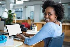 使用膝上型计算机的女性图表设计师在创造性的办公室 库存图片
