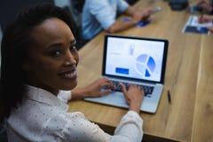 使用膝上型计算机的女性执行委员在会议室 免版税库存照片