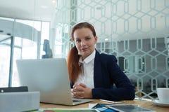 使用膝上型计算机的女性执行委员画象在书桌 免版税库存图片
