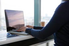 使用膝上型计算机的女性执行委员的中间部分在书桌 库存图片