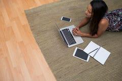 使用膝上型计算机的女性执行委员,当说谎在地毯时 库存图片