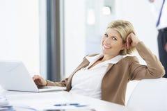 使用膝上型计算机的女性执行委员画象放松在办公室 免版税库存照片