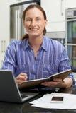 使用膝上型计算机的女性自由职业者的工作者画象在厨房在H 免版税库存照片