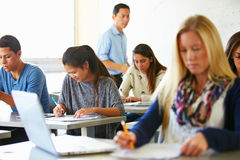 使用膝上型计算机的女性高中学生在类 免版税库存图片