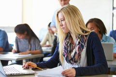 使用膝上型计算机的女性高中学生在类 免版税库存照片