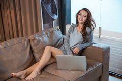 使用膝上型计算机的好女孩坐在屋子里 库存图片
