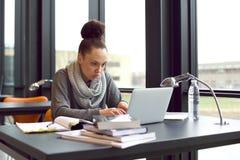 使用膝上型计算机的妇女为采取笔记对研究 图库摄影
