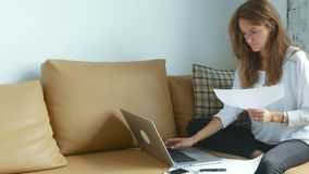 使用膝上型计算机的妇女和与文件一起使用 股票录像