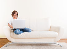 使用膝上型计算机的妇女和喝从杯子 免版税库存照片