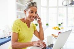 使用膝上型计算机的妇女和在家谈话在电话在厨房 免版税库存图片